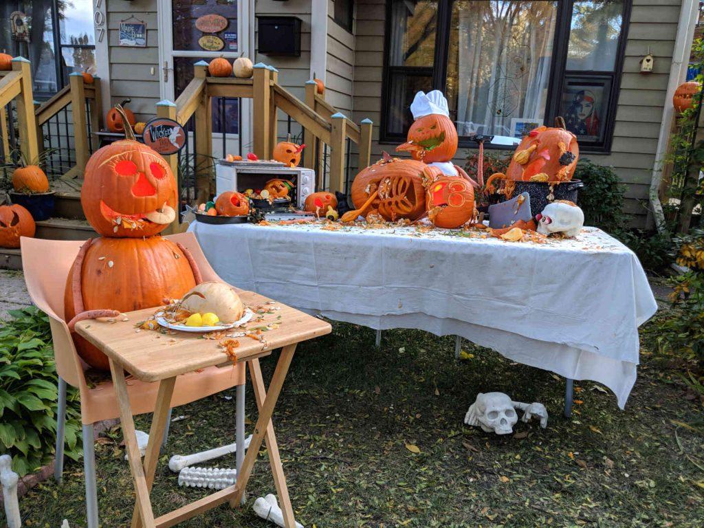 Carved pumpkin display with pumpkins eating pumpkins