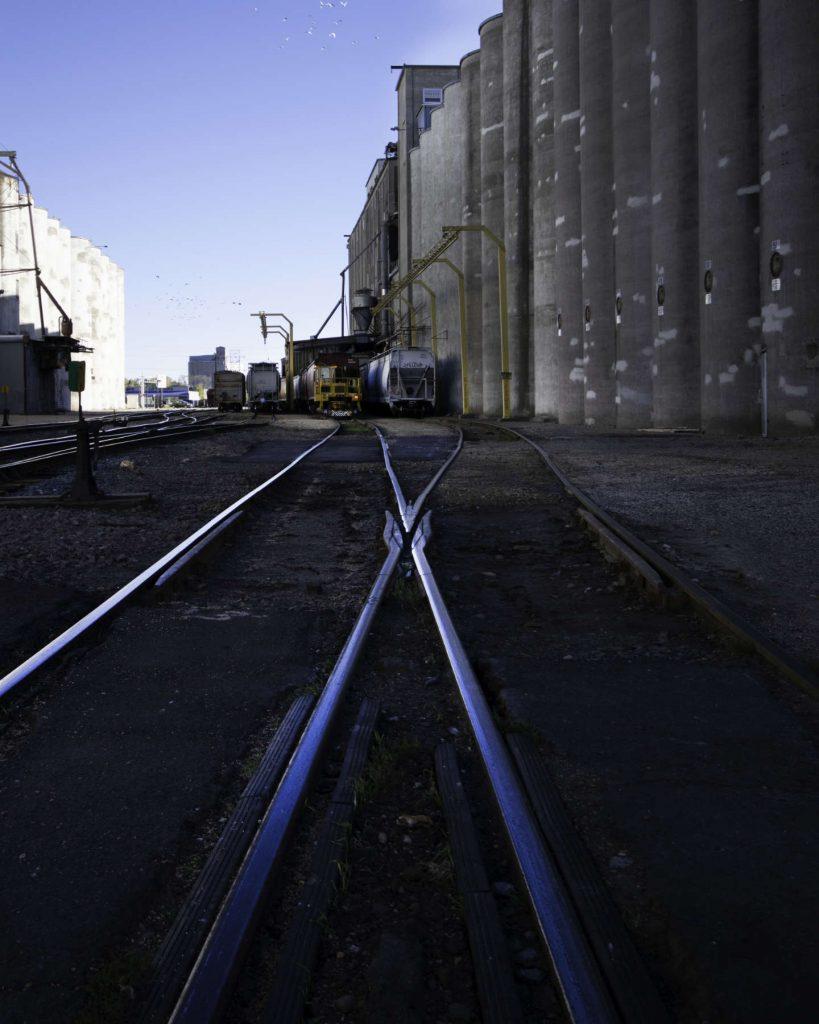 Train tracks with grain elevators in background