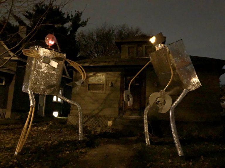 silvery robots in dark yard
