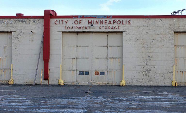 Cinder block building with City of Minneapolis Equipment Storage sign over industrial overhead door