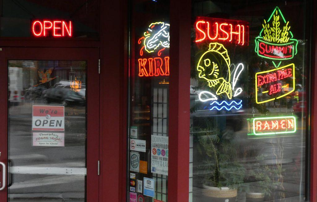 Neon signs in storefront door and windows reading OPEN, SUSHI, RAMEN