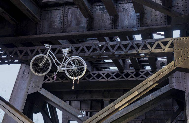 white coaster bicycle hanging under a dark gray metal superstructure under a bridge