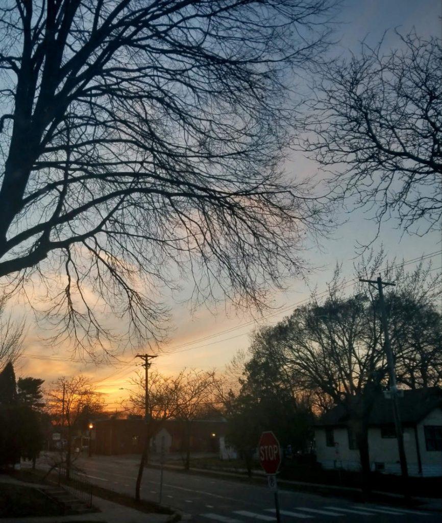fading sunset on horizon in a darkening city street