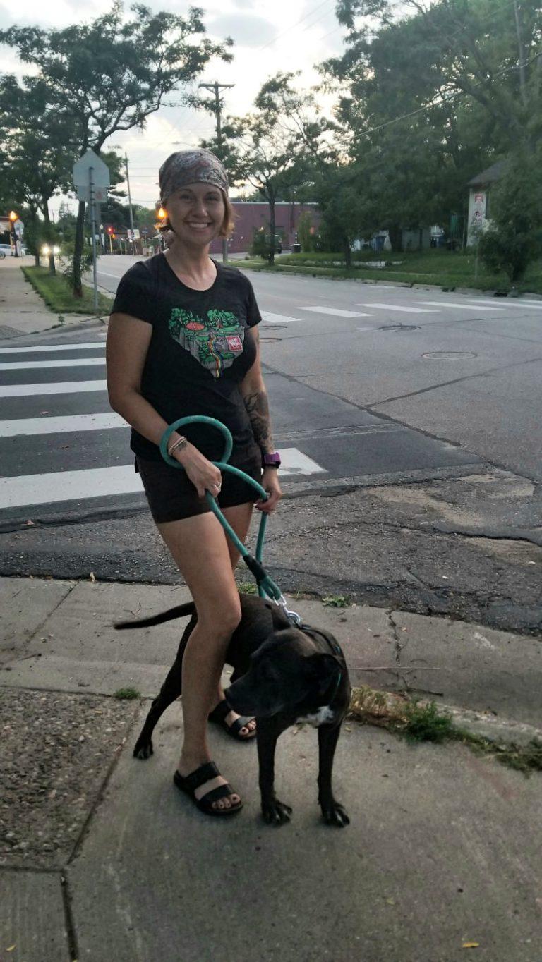 young woman in black shorts and shjirt walking a black dog on a sidewalk at street corner crosswalk