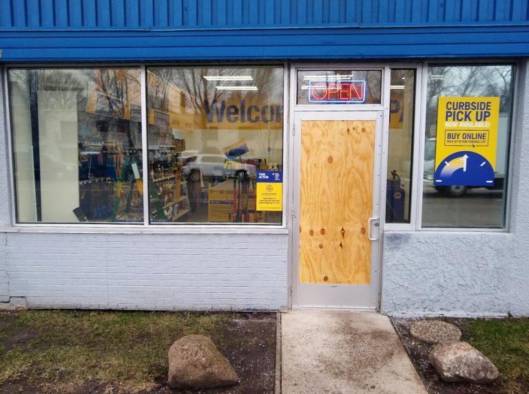 store door boarded up, interior showing through windows, neon OPEN sign over door
